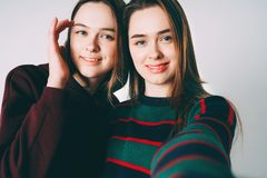 Two sisters twins beautiful girls in casual taking selfie on fro. Two sisters twins beautiful girls in casual clothes taking selfie on frontal camera of royalty free stock images