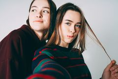 Two sisters twins beautiful girls in casual taking selfie on fro. Ntal camera of smartphone on grey background isolated stock image