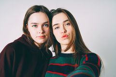 Two sisters twins beautiful girls in casual taking selfie on fro. Ntal camera of smartphone on grey background isolated stock photo