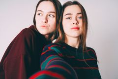 Two sisters twins beautiful girls in casual taking selfie on fro. Ntal camera of smartphone on grey background isolated royalty free stock photo