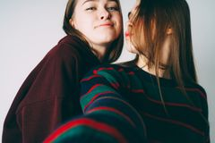 Two sisters twins beautiful girls in casual taking selfie on fro. Ntal camera of smartphone on grey background isolated, selective focus royalty free stock photo