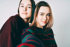 Two sisters twins beautiful girls in casual taking selfie on fro. Ntal camera of smartphone on grey background isolated royalty free stock photos