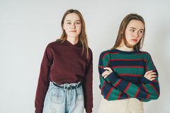 Two sisters twins beautiful girls hipsters in casual clothing. Antipodes smiling and sad on grey background isolated royalty free stock image