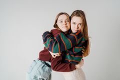 Two sisters twins beautiful girls hipsters in casual clothing on. Grey background isolated, concept love, friendship, soul mates stock photo