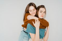 Two sisters twins beautiful girls hipsters in casual clothing on. Grey background isolated, concept love, friendship, soul mates royalty free stock image