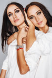 Two sisters twins emotional posing, making photo selfie, dressed same white shirt, diverse hairstyle, bright makeup Stock Photos