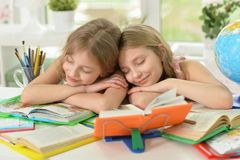 Two sisters twins fall asleep. While doing homework Royalty Free Stock Images