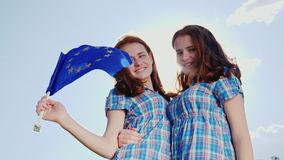 Two sisters twins with the flag of the European Union. Look at the camera, smile stock footage