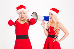 Two sisters twins having fun with megaphone Royalty Free Stock Photo