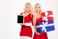 Two sisters twins holding gifts and blank screen tablet computer Stock Photo