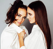 Two sisters twins posing, making photo selfie, dressed same whit Stock Images