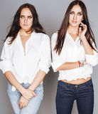 Two sisters twins posing, making photo selfie Stock Photos