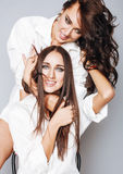 Two sisters twins posing, making photo selfie, dressed same white shirt, diverse hairstyle Royalty Free Stock Photos