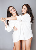 Two sisters twins posing, making photo selfie, dressed same white shirt, diverse hairstyle Royalty Free Stock Photo