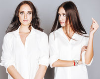 Two sisters twins posing, making photo selfie, dressed same white shirt, diverse hairstyle friends Stock Photography