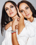 Two sisters twins posing, making photo selfie, dressed same white shirt, diverse hairstyle friends Royalty Free Stock Image