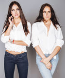 Two sisters twins posing, making photo selfie, dressed same white shirt, diverse hairstyle friends Stock Image