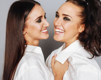 Two sisters twins posing, making photo selfie, dressed same white shirt, diverse hairstyle friends Stock Photo