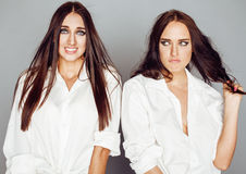Two sisters twins posing, making photo selfie, dressed same white shirt, diverse hairstyle friends Royalty Free Stock Photography