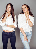 Two sisters twins posing, making photo selfie, dressed same white shirt, diverse hairstyle friends Royalty Free Stock Images