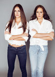 Two sisters twins posing, making photo selfie, dressed same white shirt, diverse hairstyle friends Royalty Free Stock Photo
