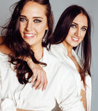Two sisters twins posing, making photo selfie, dressed same white shirt, diverse hairstyle friends Royalty Free Stock Photos