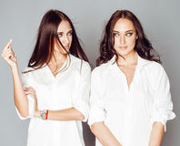Two sisters twins posing, making photo selfie, dressed same white shirt, diverse hairstyle friends, lifestyle people Stock Photo