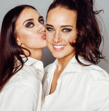 Two sisters twins posing, making photo selfie, dressed same white shirt, diverse hairstyle friends, lifestyle people Stock Photography