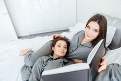 Two sisters twins reading book and lying on bed together Royalty Free Stock Images