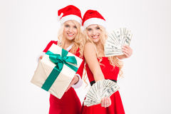 Two sisters twins in red santa claus costumes and hats Stock Photo