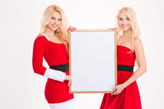 Two sisters twins in santa claus clothes with blank board Stock Photo