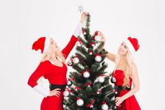 Two sisters twins in santa claus costumes decorating Christmas tree Royalty Free Stock Image