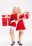 Two sisters twins in santa claus costumes  holding big gifts Stock Images