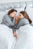 Two sisters twins sleeping in bedroom together Stock Images