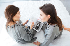 Two sisters twins talking and reading magazine in bedroom Stock Photography