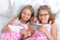 Two sisters twins using smart phones. Wearing eyeglasses Stock Photography
