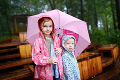 Two sisters under umbrella Stock Images