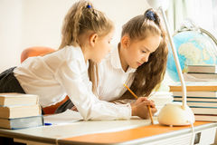 Two sisters in uniform doing homework Stock Photography