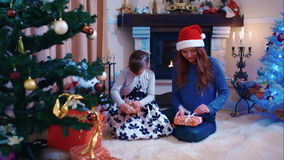 Two sisters unpacking their Christmas gifts. Winter holidays Christmas and New Year stock footage