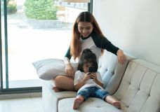 Two sisters use mobile phone and sitting at sofa in house with r Stock Image