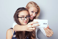 Two sisters using smart phone for selfie. Stock Photo