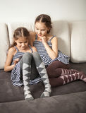 Two sisters using tablet on couch Royalty Free Stock Images