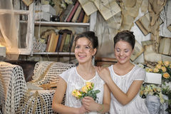 Two sisters in vintage white dress. With a bouquet of yellow roses Stock Photography