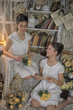 Two sisters in vintage white dress. With a bouquet of yellow roses Stock Image