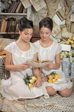 Two sisters in vintage white dress with a bouquet of yellow roses. Read the book Royalty Free Stock Photos