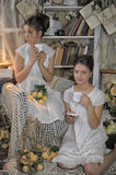 Two sisters in vintage white dress drink coffee Stock Photos