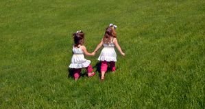 Leadership Qualities. Two sisters walk across a grassy field.  The older sibling is in the lead showing leadership qualities.  The younger one follows.  They Royalty Free Stock Photos
