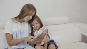 Two sisters watching tablet PC, sitting on sofa and play games, small young baby and adult sister. Two sisters watching tablet PC stock footage