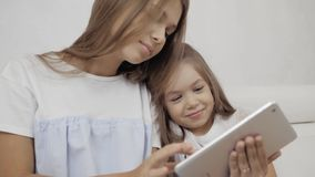 Two sisters watching tablet PC, sitting on sofa and play games, small young baby and adult sister. Two sisters watching tablet PC stock video footage