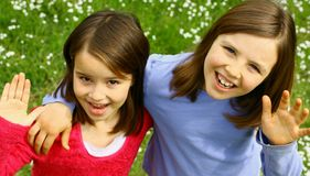 Two sisters waving Stock Images
